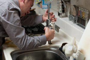 Plumber fixing a tap