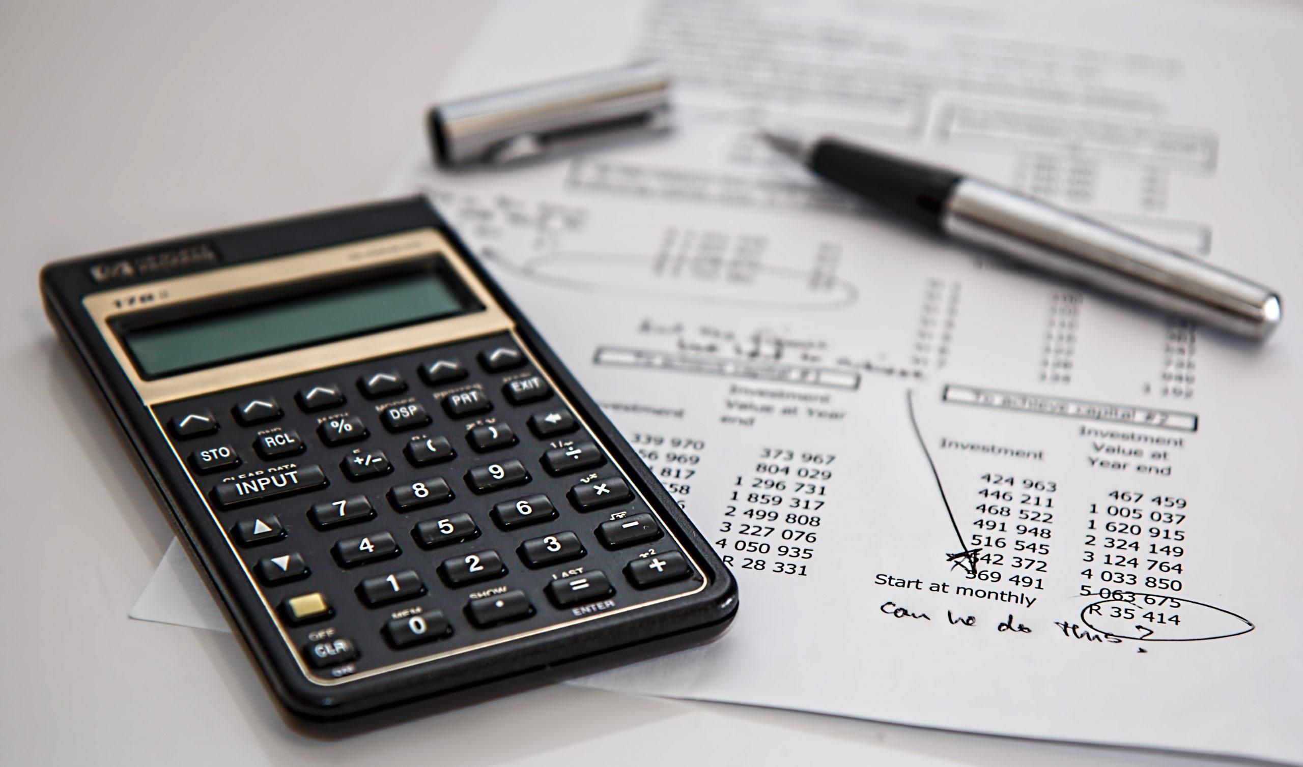 calculator, pen and accounting sheets