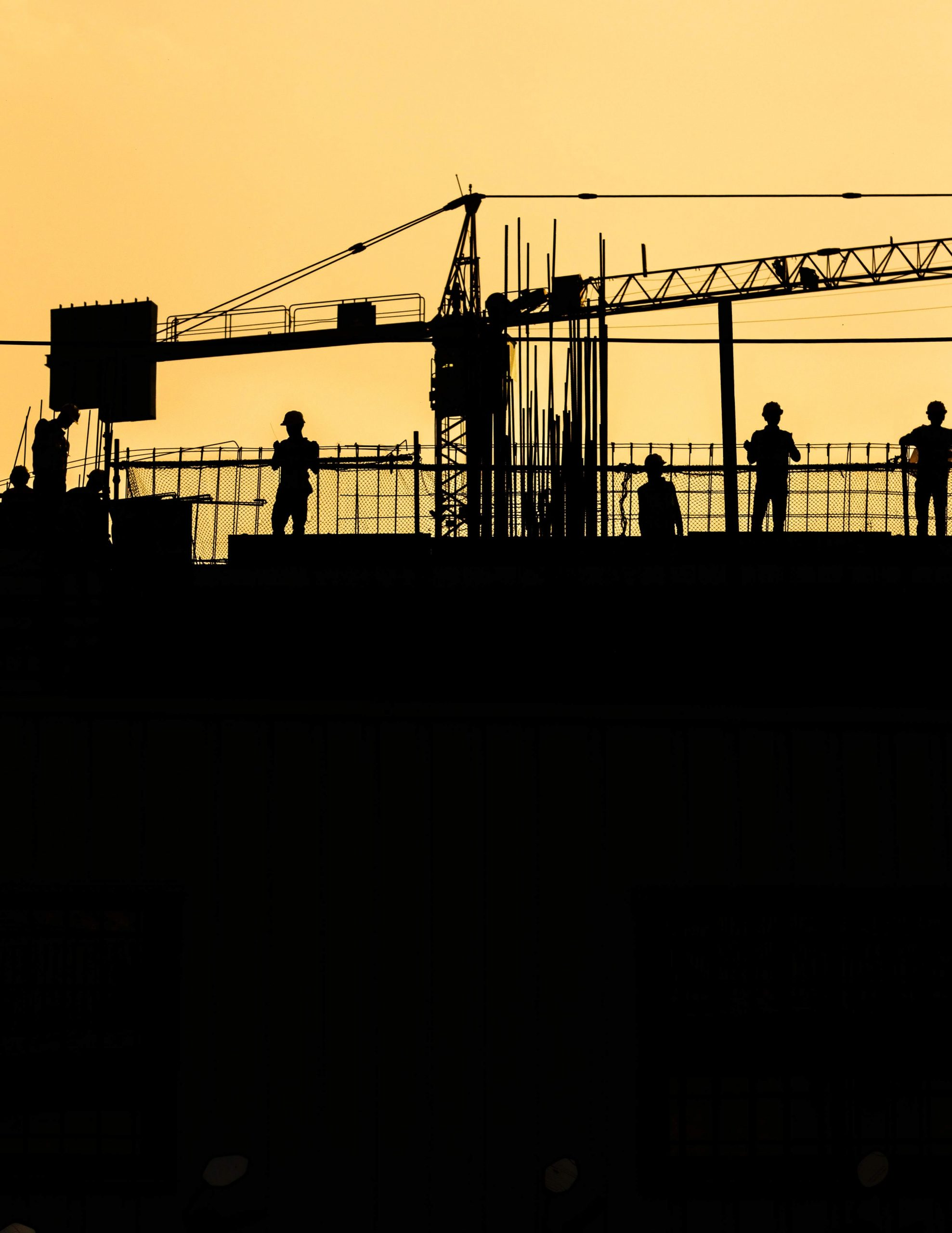 Construction workers silhouetted at sunset